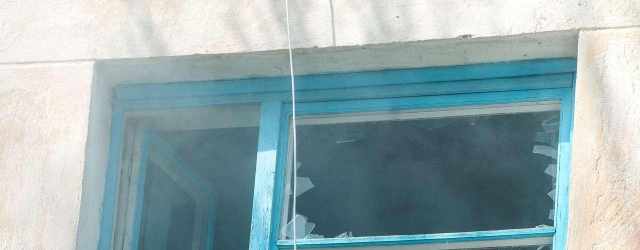22 de março - Soldado ucraniano observa movimento através de uma janela quebrada em Novofedoricka. Cerca de 200 soldados pró-Moscou invadiram base da Ucrânia neste sábado