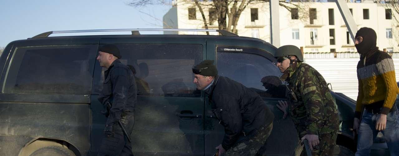 22 de março - Soldados pró-russos escondem atrás de carro na base militar aérea de Sebastopol