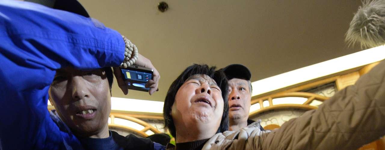 24 de março -Membro da família de um passageiro a bordo do vôo MH370 da Malaysia Airlines chora depois de assistir a transmissão da entrevista coletiva, em que o governo malaio confirmou que o avião caiu no oceano Índico. Foto tiradano hotel Lido, em Pequim, na segunda-feira, 24 de março