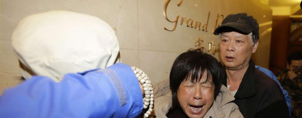 24 de março - Membro da família de um passageiro a bordo do vôo MH370 da Malaysia Airlines chora depois de assistir a transmissão da entrevista coletiva em que o governo malaio confirmou que o avião caiu no oceano Índico. Foto tiradano hotel Lido, em Pequim, na segunda-feira, 24 de março