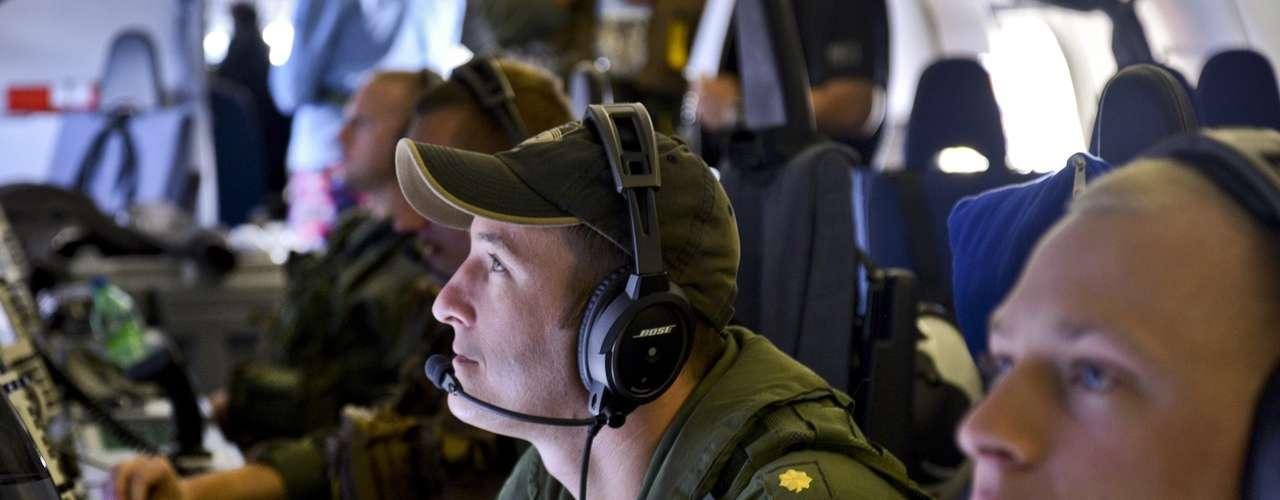 24 de março - Oficiais americanos monitoram estação de trabalho, em um P-8A Poseidon, durante operações de busca do vôo MH370 da Malaysia Airlines