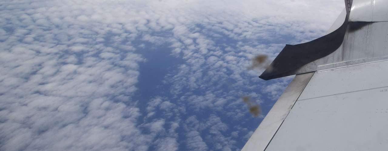 27 de março - excesso de combustível é despejado de um bico que se projeta da asa esquerda de um avião da Força Aérea Australiana antes do pouso, depois de participar demissão debusca