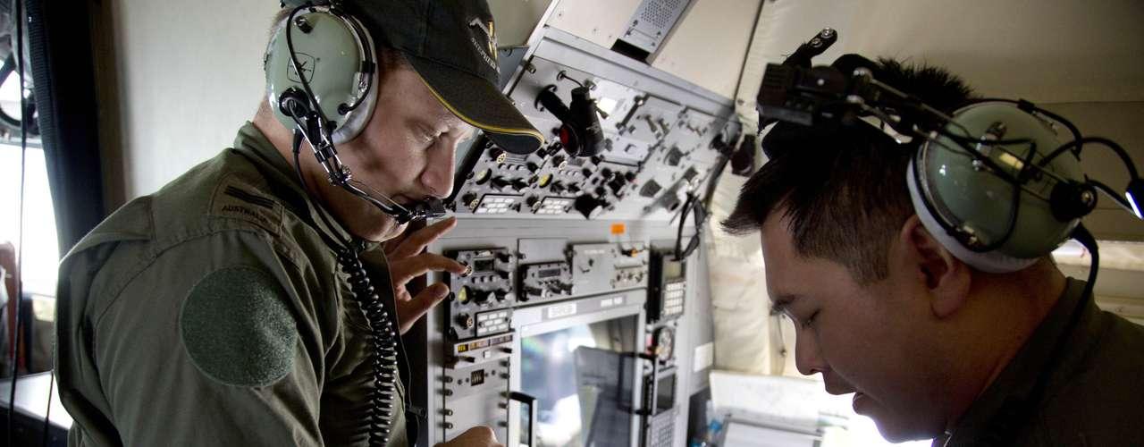 27 de março - Membros da tripulação a bordo de um Air Force AP-3C Orion da Força Aérea Australiana observammapas de navegação, durante operação de busca pelo Boeing da Malaysian Airlines sobre o Oceano Índico meridional