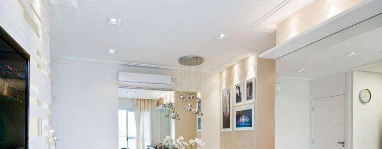 O painel de madeira da TV também funciona como parede texturizada. Mas como os tons da sala são neutros, o ambiente não fica carregado