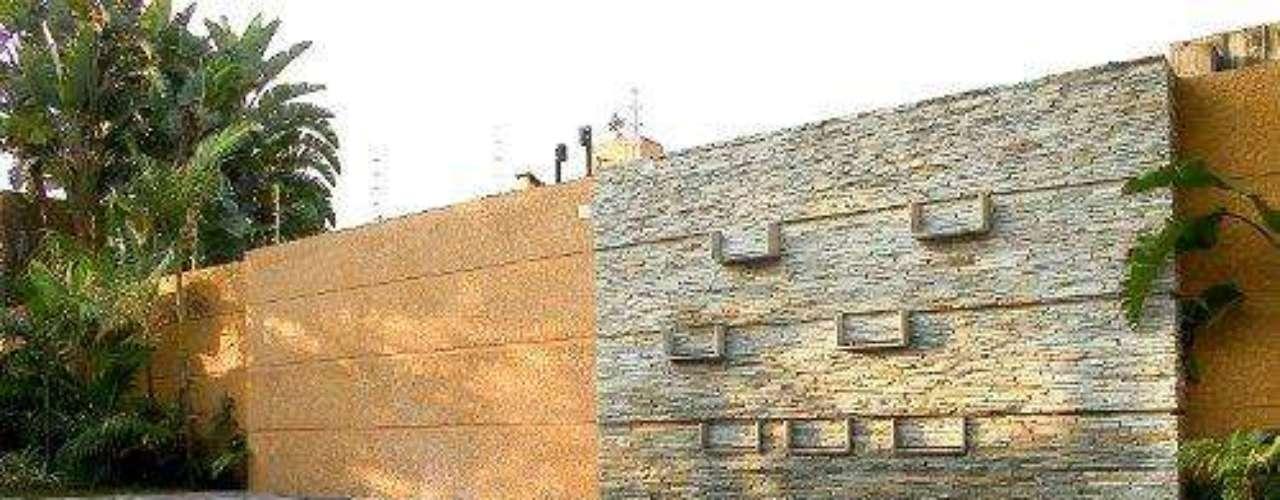 O paredão de pedra foi combinado à parede texturizada cor de telha. A localização é ideal porque, dessa maneira, os respingos da piscina não mancham a parede