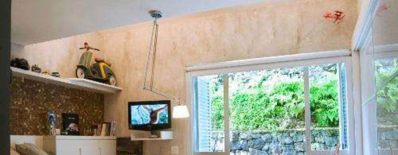 A parede copiando mármore combina com a mureta de pedra no fundo da foto e, principalmente, com a decoração básica do quarto