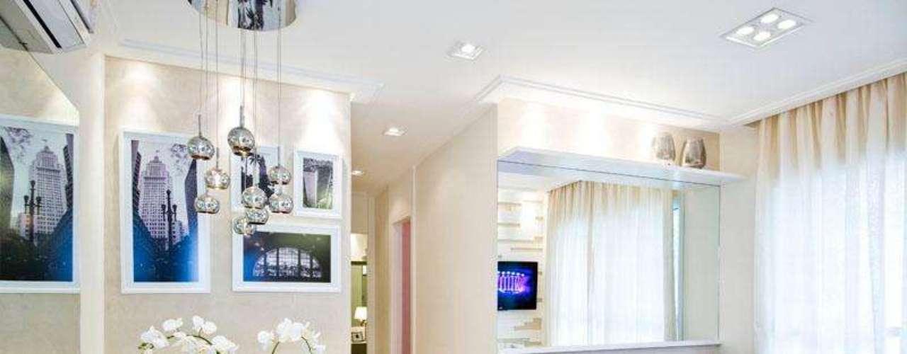 Como a sala é pequena, a solução foi usar cores neutras. Aí, dá para usar acessórios mais ousados como o lustre e os quadros