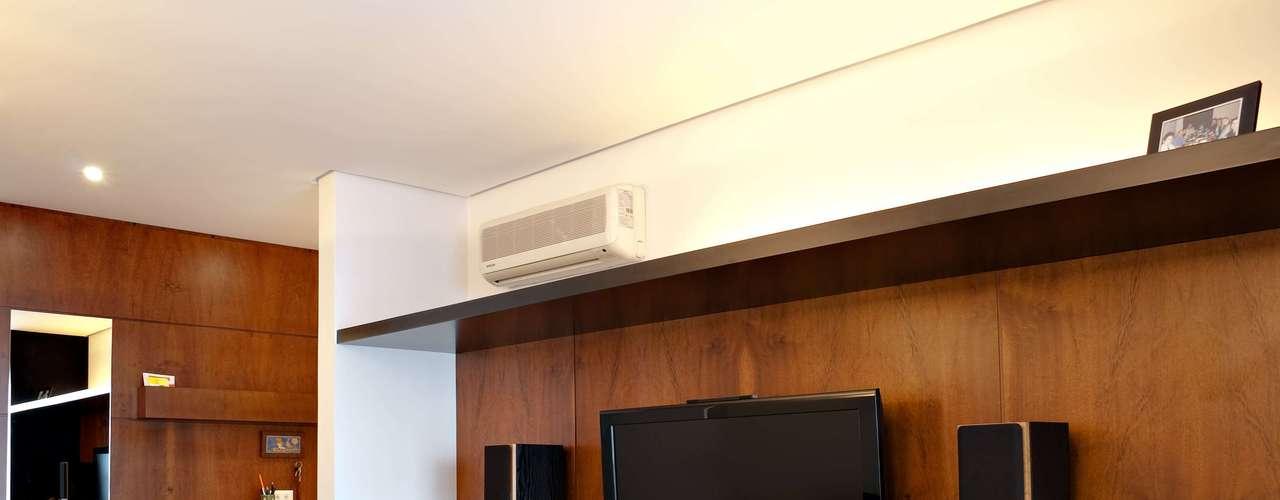 Neste projeto, também do escritório schüssel quezada, o painel de madeira também serve para esconder a fiação do home theater