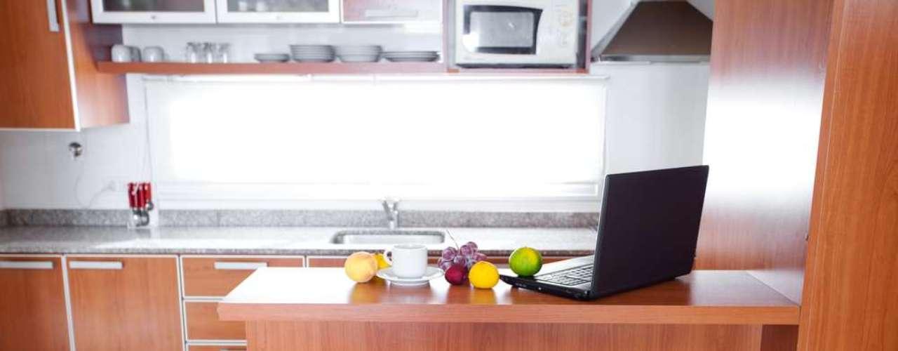 Além de servir como bancada para refeições, o balcão de uma cozinha americana pode ser um local improvisado de trabalho