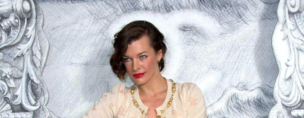 Milla Jovovich posa com scarpins rosa de plataforma e bicos em tom vinho