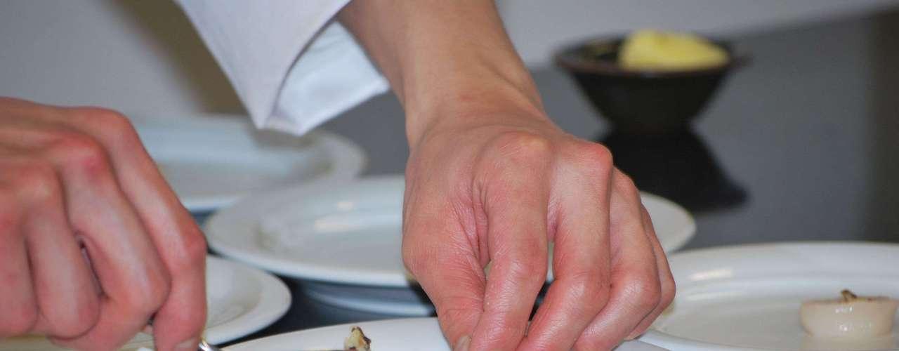 Murakami passa a manteiga de trufa com os dedos na parte de cima das vieiras. \