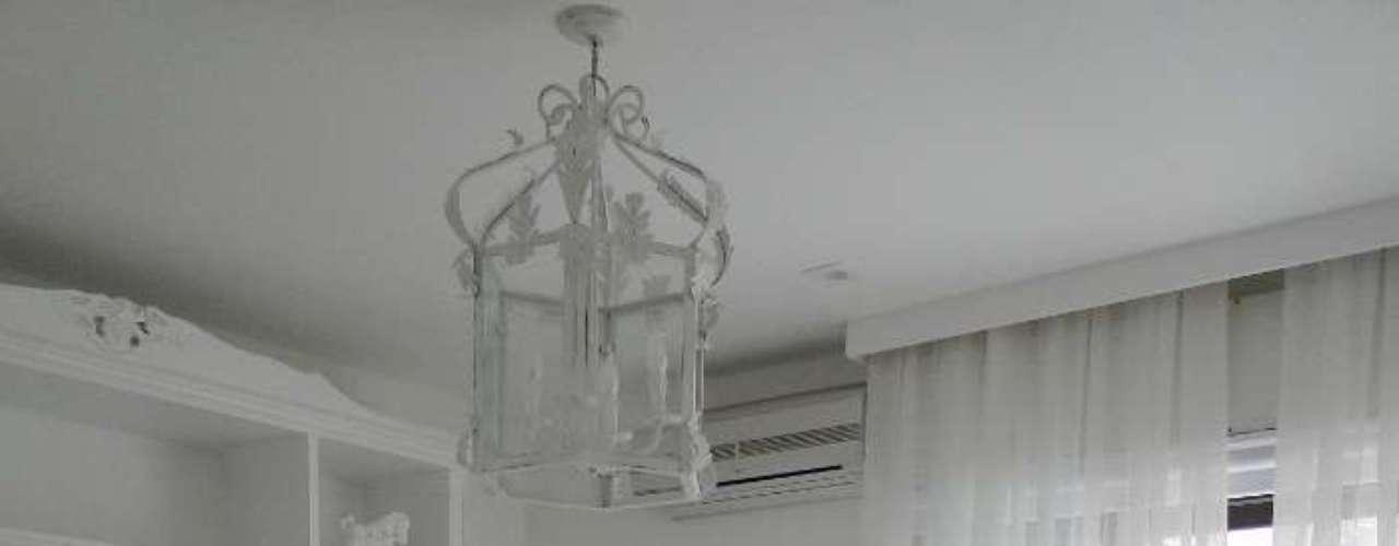 Como a decoração do quarto é clássica e clean ao mesmo tempo, dá para ousar nos detalhes, como o lustre em forma de gaiola