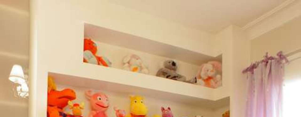 A parede comporta uma mesa de alvenaria e nichos embutidos para guardar os brinquedos