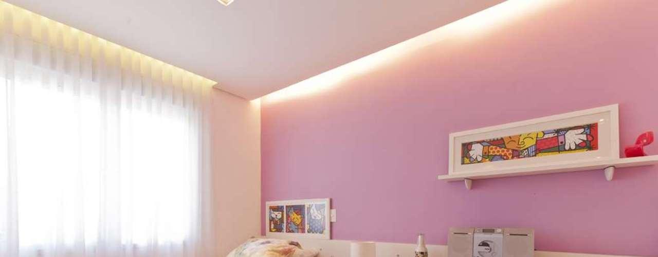 O mobiliário branco acompanha a parede rosa e os quadros coloridos