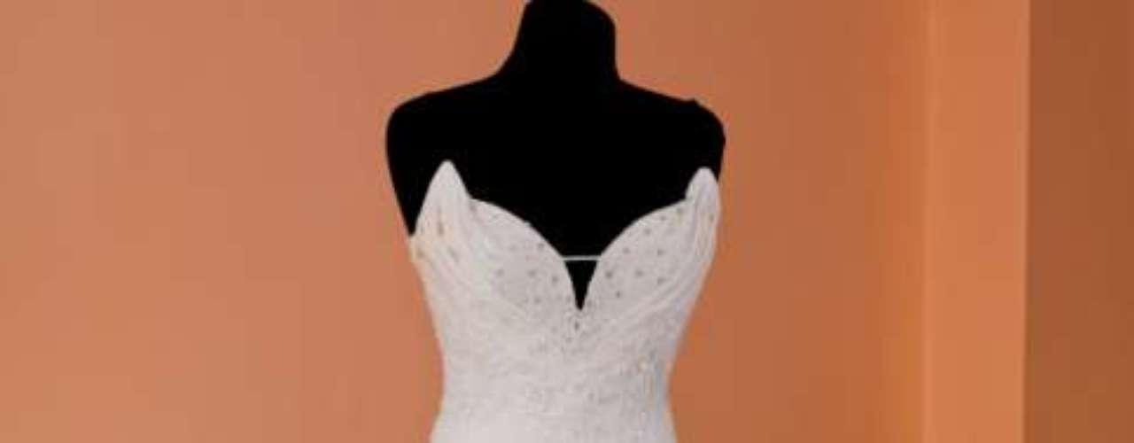 Escolha um vestido mais ajustado: modelos com saias amplas, com silhueta em forma de A, são bem tradicionais. Mas vestido mais ajustados, que são mais abertos apenas a partir das coxas, desenham bem a silhueta e estão se tornando muito populares