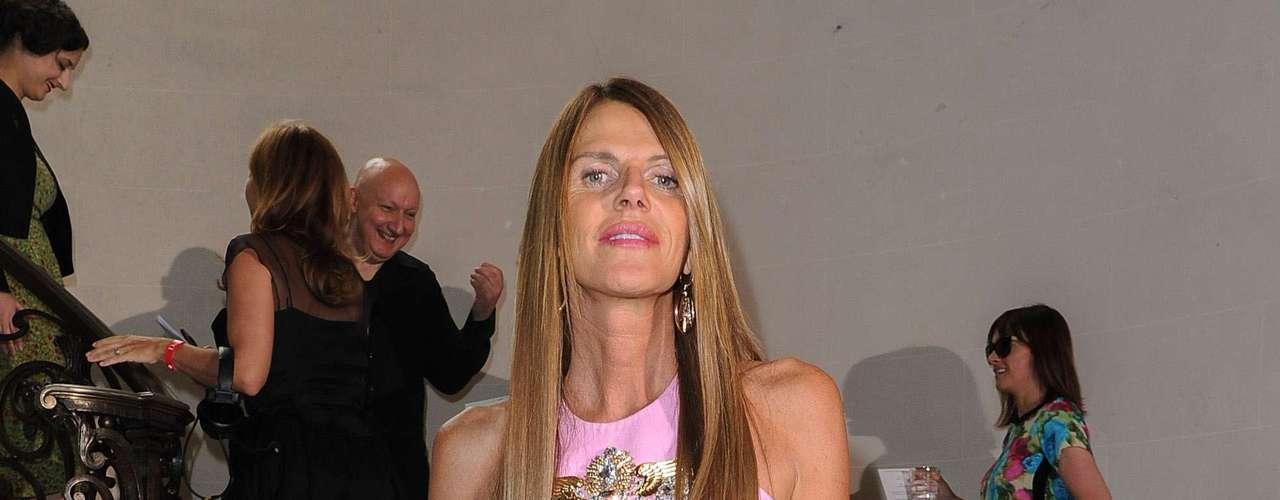 Anna Dello Russo usa vestido na cor rosa do estilista Fausto Puglisi. A editora tem o mesmo modelo na cor branca