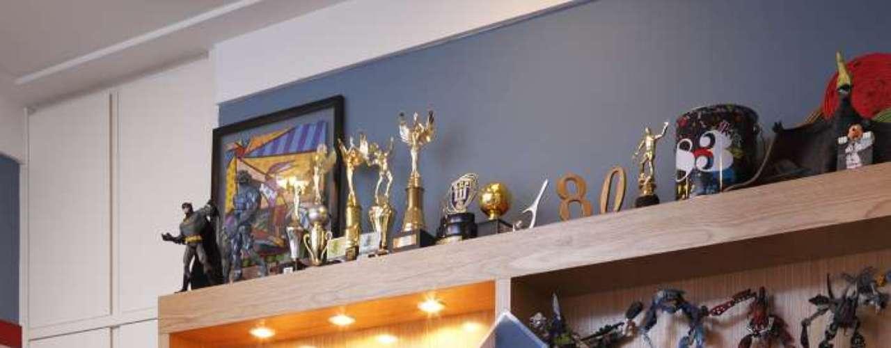 Neste ambiente a grande estante guarda os brinquedos, expõe os troféus e ainda abriga a TV