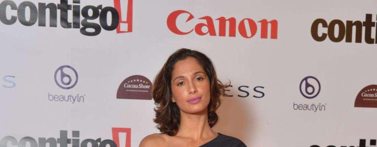 Camila Pitanga posa com vestido mais larguinho com apenas uma manga de tecido opaco, que ganhou sofisticação com o uso de cinto com metal dourado e clutch durinha, mais formal
