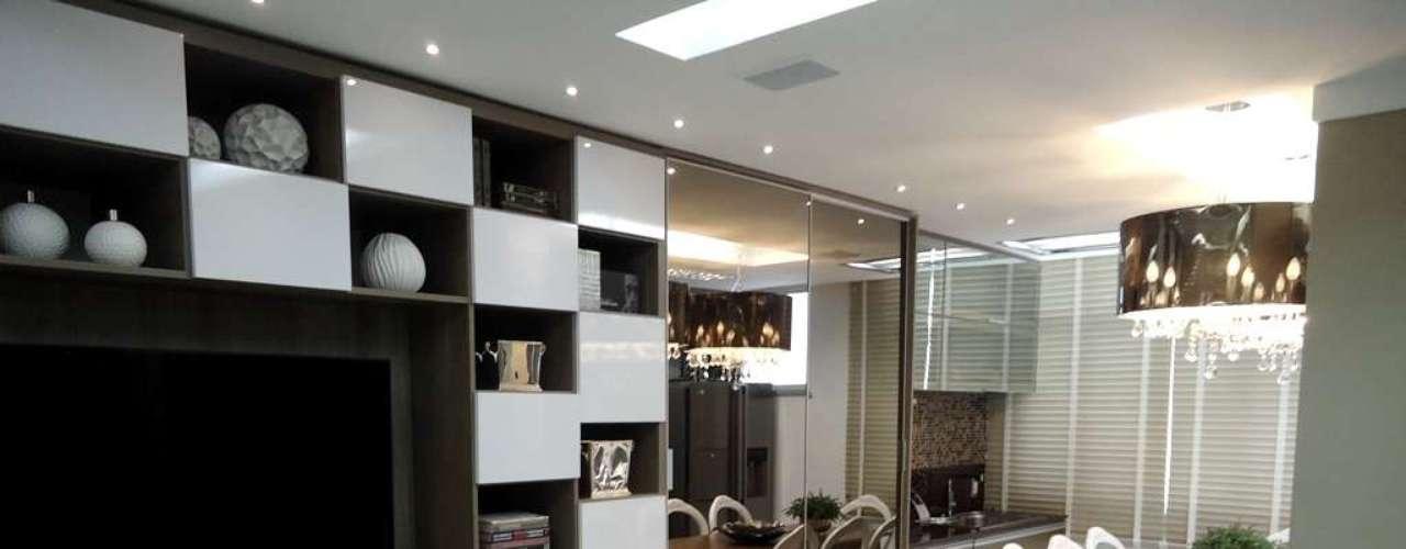 Outro projeto de Thoni Litsz em que a parede do corredor entre cozinha e sala é aproveitada com armários, desta vez espelhados