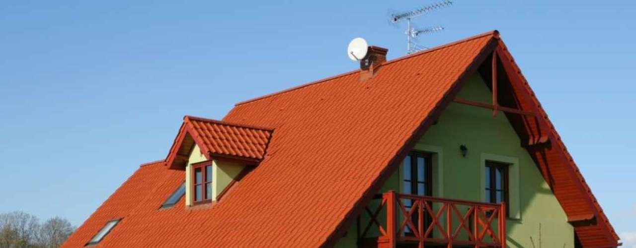 Aqui, o alaranjado do telhado e da madeira escolhida para a sacada contrasta com o verde das paredes