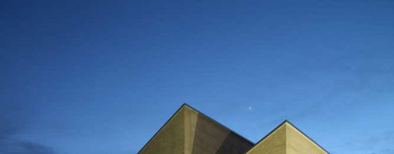 Outra dica é pensar nos efeitos que a luz provoca nas cores. A foto mostra a mudança que a iluminação amarelada provoca numa parede de concreto aparente