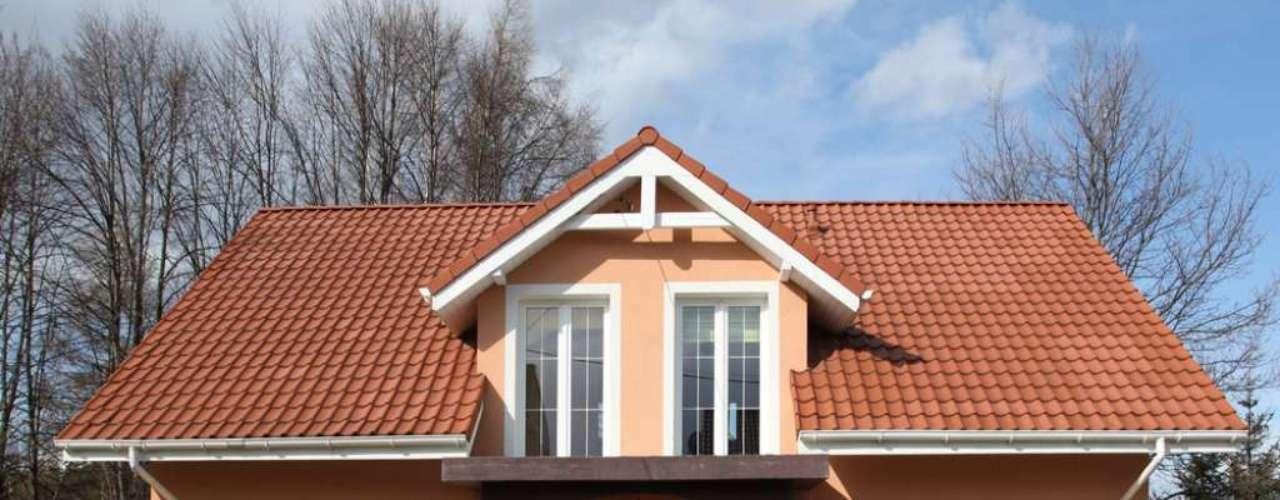 Nesta casa, a proposta foi a harmonia entre as cores. A combinação do rosado da fachada com o branco das portas e janelas é suave