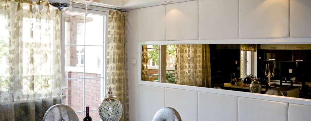 O espelho horizontal reflete a cozinha e ajuda a integrar o espaço com a sala de jantar
