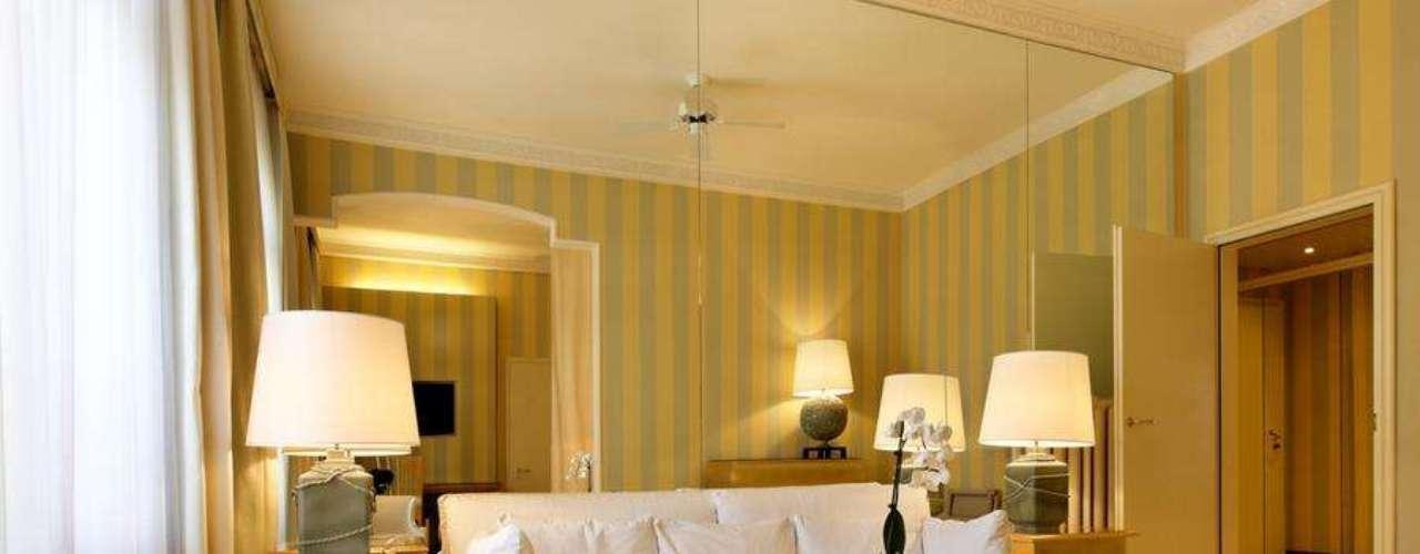 Junto com as listras verticais, a parede inteira revestida com espelhos ajuda a dar a sensação de um ambiente mais amplo