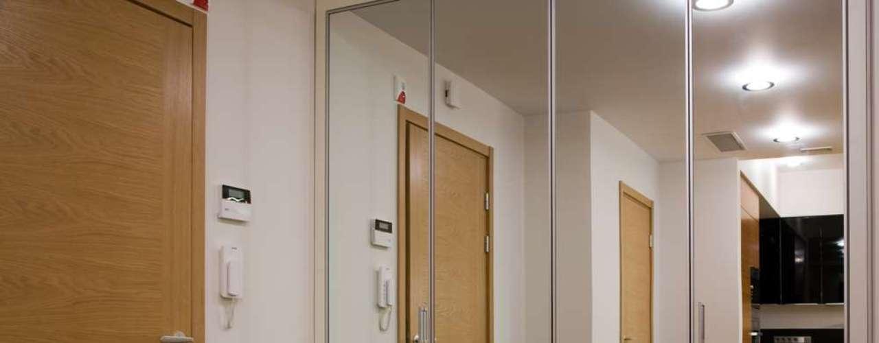 Logo na entrada do apartamento, a parede espelhada dá a ilusão de um espaço maior e permite ter uma visão da cozinha
