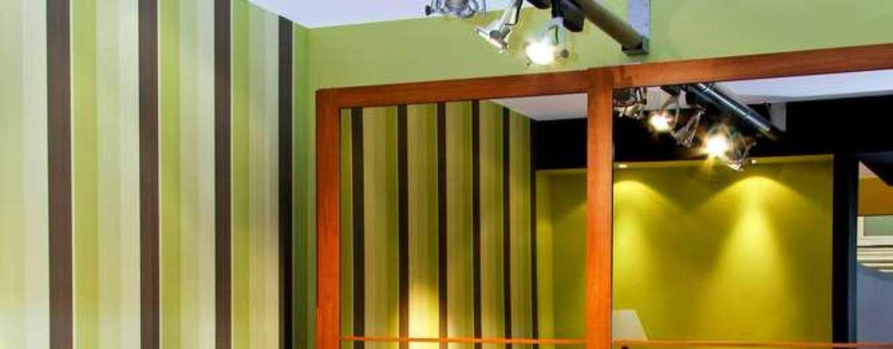 Além do espelho, as listras verticais na parede ajudam a fazer o quarto parecer mais amplo