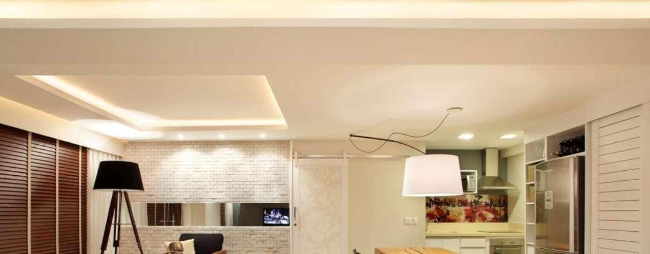 As arquitetas Gabriela Eloy e Carolina Travaglini integraram cozinha, sala de estar e uma sala de TV. Carolina explica que o espelho faz com que seja possível ter uma visão de todo o espaço estando em qualquer um desses ambientes