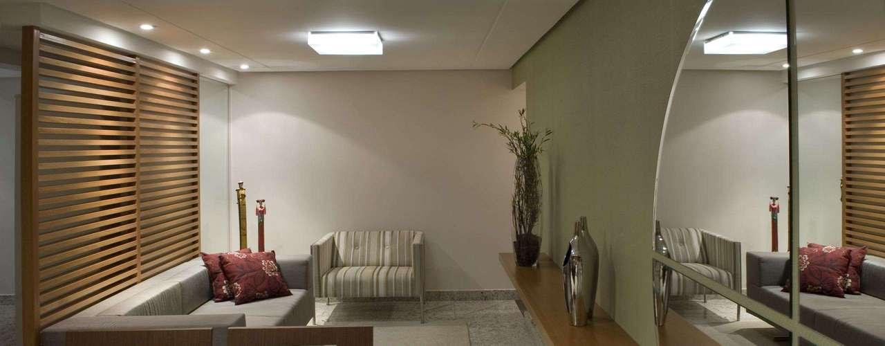 Juntas, esta sala de estar e de jantar ocupam 21 metros quadrados. O espelho reflete outra área interna da casa e ajuda a dar maior sensação de amplitude