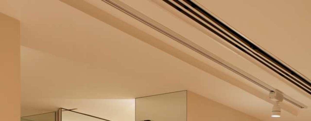 Aqui, a arquiteta escondeu a entrada deste banheiro cobrindo a porta e a parede com espelhos. O banheiro ficava logo na entrada do apartamento, e a ideia do espelho dá um pouco mais de conforto para quem entra, explica Paloma Yamagata
