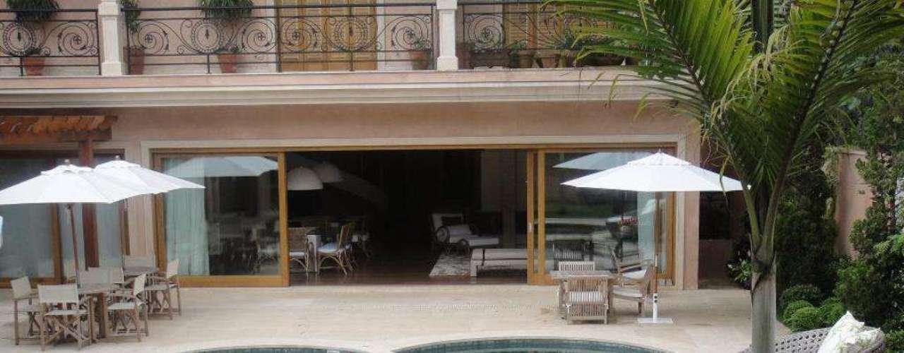 Cadeiras e poltronas no espaço interno facilitam a integração com a área da piscina