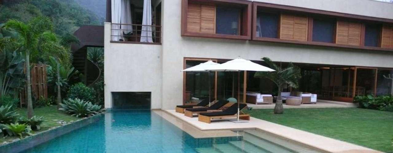 Neste projeto, o paisagista Gilberto Elkis usou uma pedra branca na borda da piscina e plantas tropicais no entorno para recriar o clima da praia dentro da casa