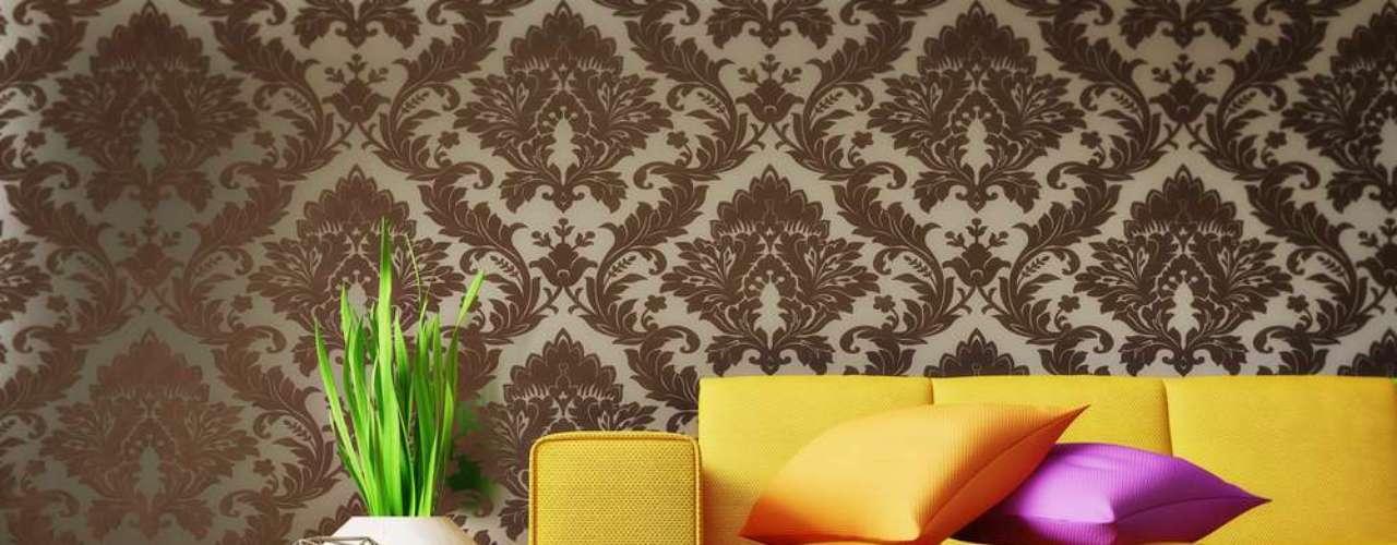 O amarelo do sofá e o colorido das almofadas, assim como o enfeite de formas inusitadas à esquerda, ajudam a quebrar a seriedade da decoração
