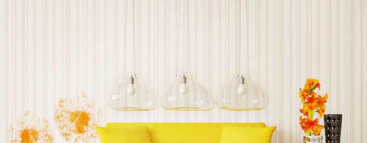 As luminárias dão o grande toque de originalidade desta sala, mas o sofá amarelo também se destaca