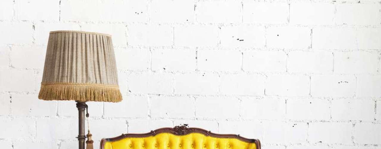 Neste projeto rústico, o amarelo do sofá se sobressai frente ao branco da parede e do piso