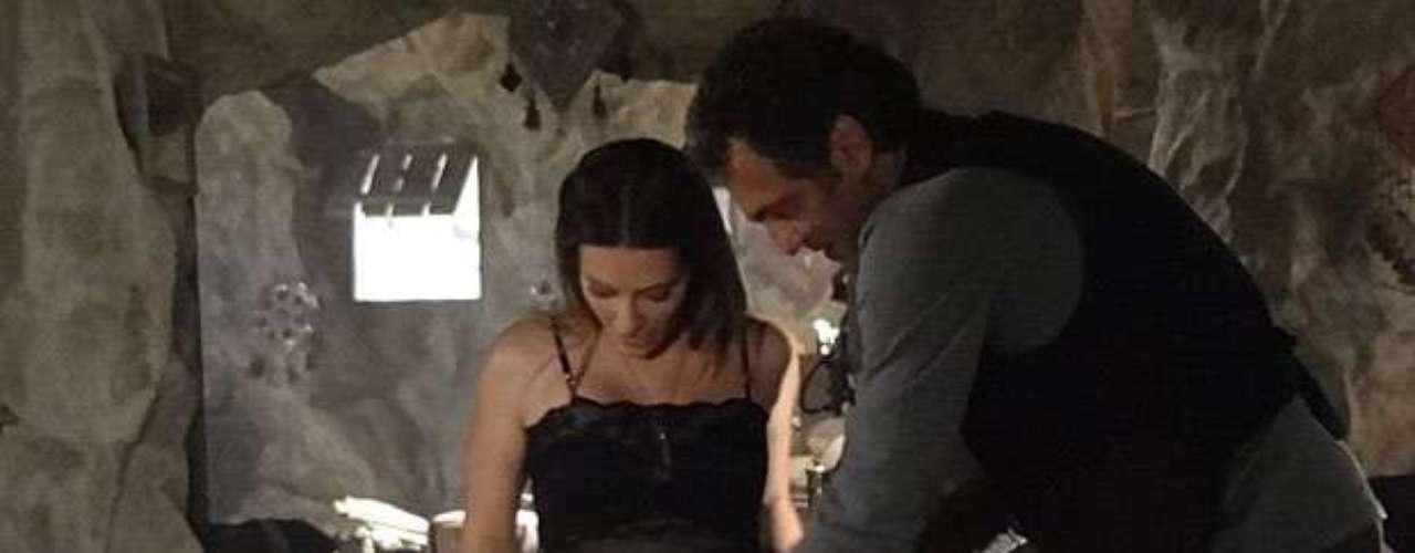 Zyah (Domingos Montagner) chega à caverna cheio de sacolas com peças típicas e as entrega para a amada, que veste de prontidão para agradá-lo