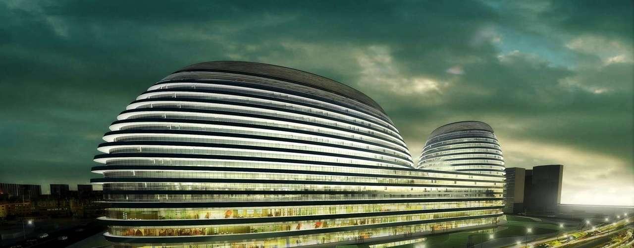 Galaxy Soho Building, Pequim, China: cada vez mais modernos, os prédios de Pequim, crescem a um ritmo desenfreado. Em 2012, uma das construções mais marcantes inauguradas na capital chinesa foi o Galaxy Soho Building, projetado pela arquiteta Zaha Hadid, num complexo de entretenimento composto por quatro estruturas futuristas abobadadas interligadas por pontes e plataforma, criando um belo conjunto de alumínio, pedra, vidro e aço inoxidável