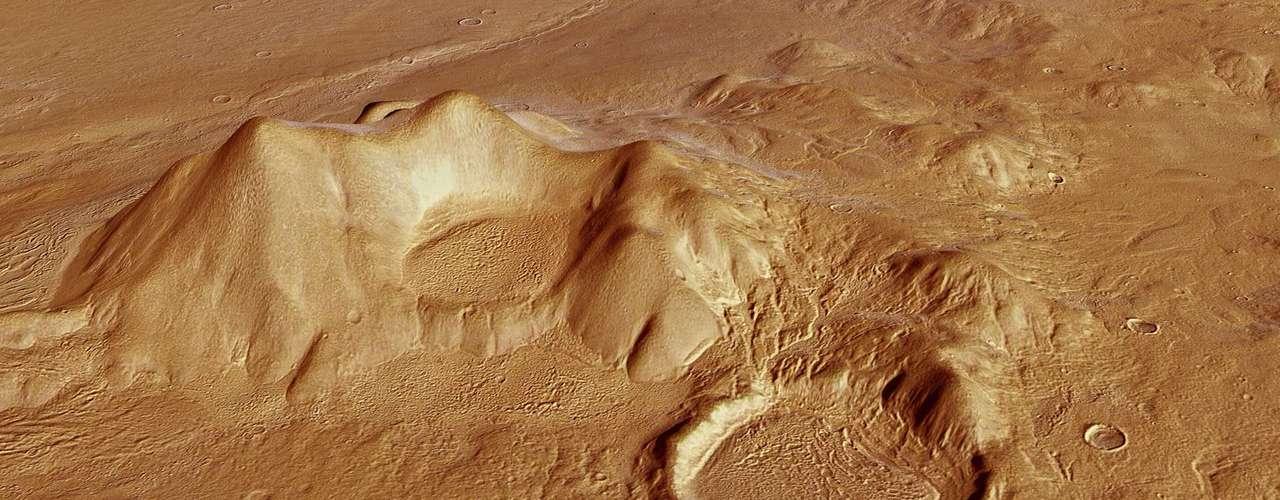 Foto gerada por computador mostra região montanhosa com grande cratera de impacto cheia de sedimentos. A inclinação da estrutura à direita pode indicar sublimação ou evaporação de gelo em diferentes períodos e níveis dentro da cratera