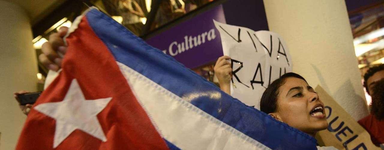 Manifestante exibe a bandeira cubana durante o tumulto causado pelo bate-papo com Yoani Sánchez