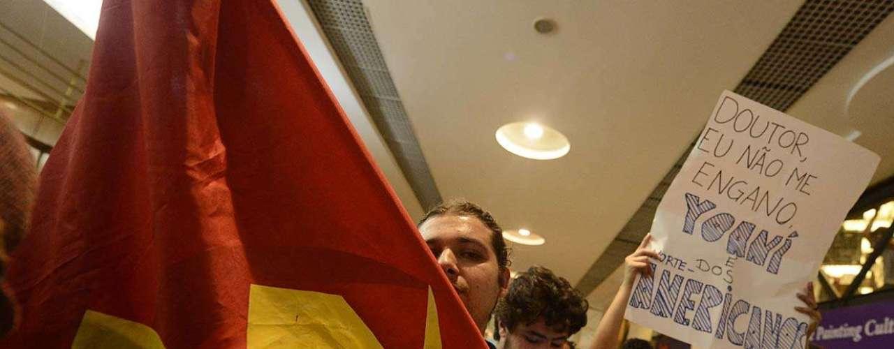 Manifestante com a bandeira soviética, ao lado de cartaz acusatório contra a blogueira cubana