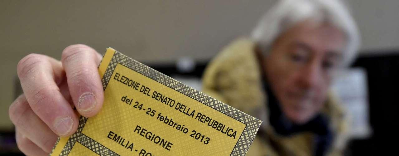 Eleitor deposita cédula na urna em Piacenza