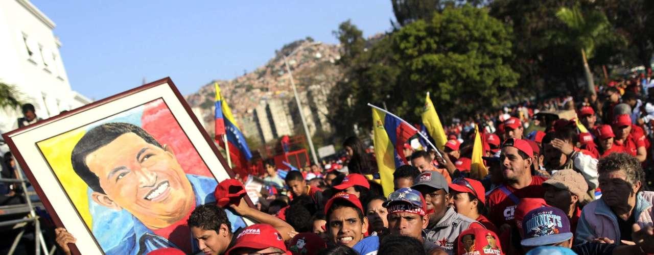 8 de março -Com imagens do ex-mandatário e bandeira, os simpatizantes de Chávez esperam para se despedir