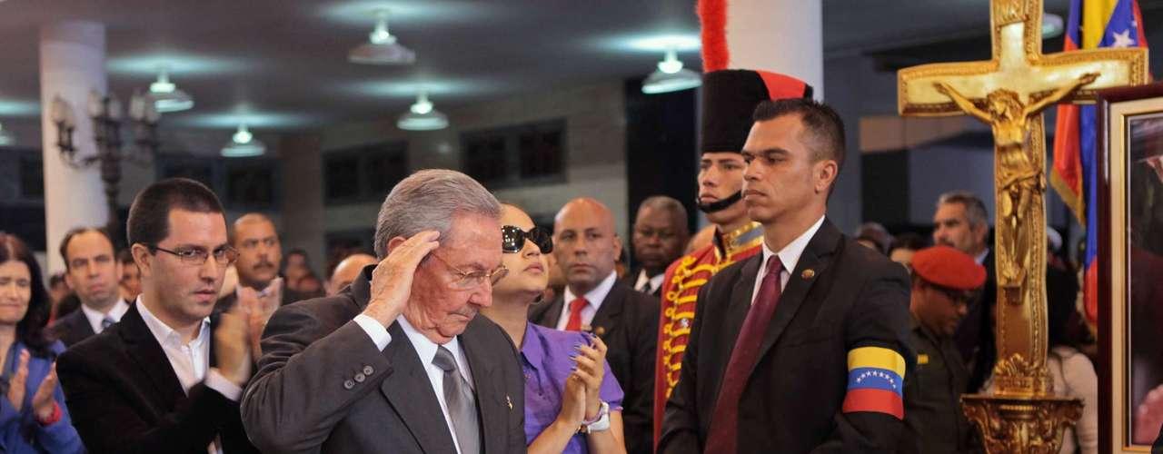 7 de março -O presidente cubano, Raúl Castro, bate continência para o caixão de Chávez durante o velório