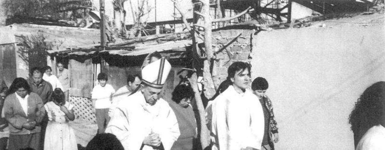 Fotografia cedida pelo grupo Ediciones B mostra Jorge Mario Bergoglio (centro) visitando o assentamento do bairro de Barracas, em Buenos Aires, na Argentina, em 2007, quando já era arcebispo da cidade