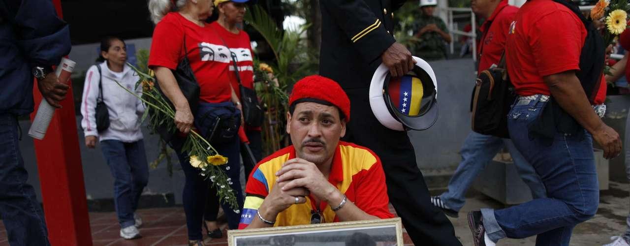 15 de março -Com foto de Chávez, seguidor aguarda para despedida final do falecido presidente