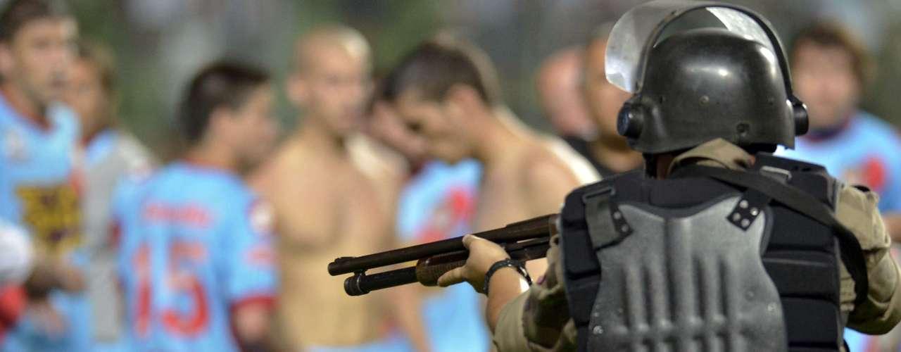 Policial aponta arma de fogo contra jogadores do Arsenal em tumulto após a vitória do Atlético-MG