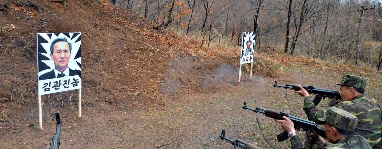 7 de abril - Imagem mostra soldados norte-coreanos praticando tiros em uma foto do Ministro de Defesa da Coreia do Sul Kim Kwan-Jin